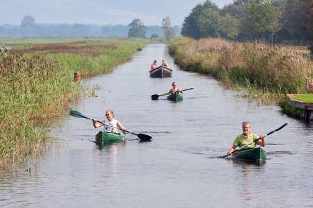 Weerribben, The Netherlands- September 03, 2011: People pedaling in canoes through wetlands of Dutch National Park Weerribben