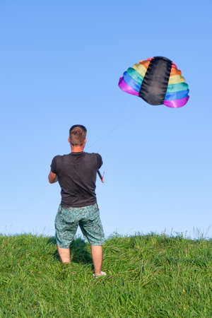 Urk, The Netherlands- August 15, 2011: Man enjoying with big colorful kite at dike near Urk
