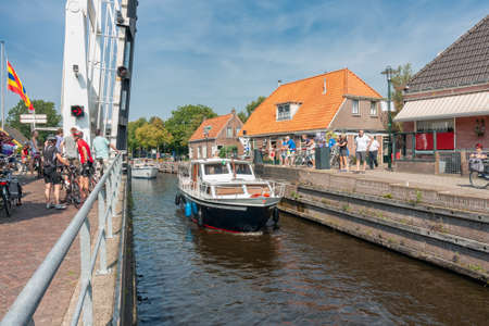 Ossenzijl, The Netherlands- September 03, 2011: Pedestrians and bikers waiting for opened bridge while yachts passing in the canal