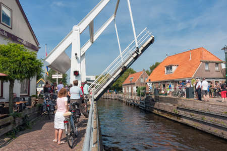 Ossenzijl, The Netherlands- September 03, 2011: Pedestrians and bikers waiting for opened bridge for yachts passing in the canal