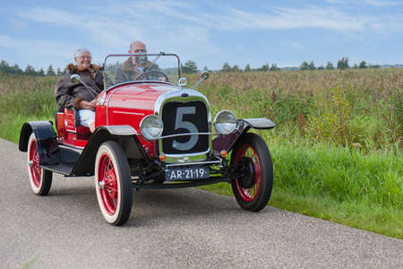 Weerribben, The Netherlands- September 03, 2011: Senior couple riding with a classic Ford oldtimer through National Park Weerribben in the Netherlands 新闻类图片