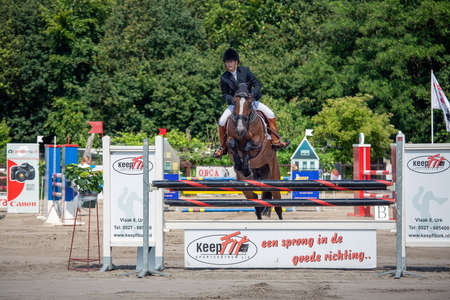 Urk, The Netherlands- July 07, 2012: Horse contest with female jockey at horse jumping over barrage at Urk, The Netherlands