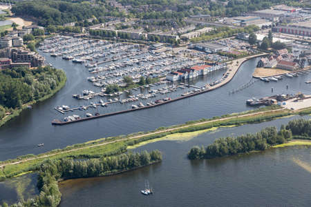 Aerial view Dutch village Huizen at lake Gooimeer with marina harbor and residential area 免版税图像