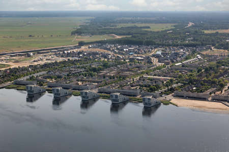 Aerial view Dutch village Huizen at lake Gooimeer with apartment buildings and residential area 免版税图像