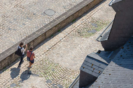 Luxembourg City, Luxembourg - August 18, 2018: View man and woman walking over medieval pavement in Grund district Luxembourg city 新闻类图片