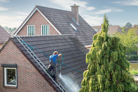 Cleaner with pressure washer at roof of house cleaning the roof tiles, removing moss and weed