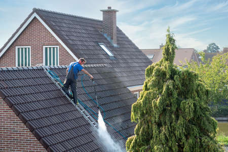 Urk, The netherlands - September 15, 2020: Cleaner with pressure washer at roof of house cleaning the roof tiles, removing moss and weed