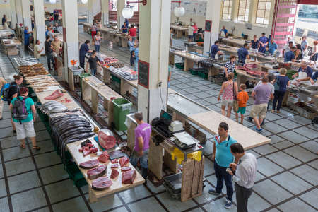 Funchal at Madeira, Portugal - August 01, 2014: Butchers saling fish at the fish market of the famous Mercado dos Lavradores in Funchal, capital city of Madeira, Portugal