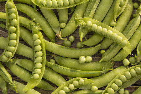 ration: pods of fresh green peas scattered on the wooden boards Stock Photo