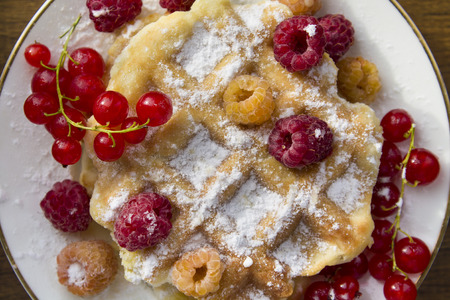 soft waffles with fresh berries, dusted with powdered sugar Stock Photo