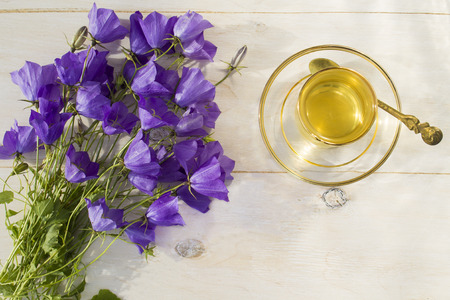 Cup of green tea in a glass Cup and a bouquet of blue bells