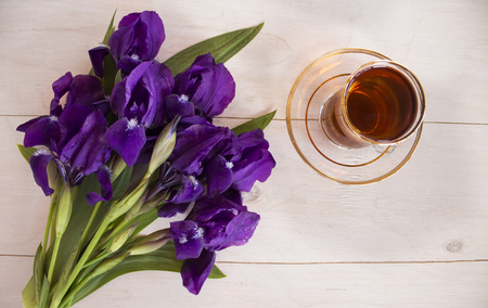 cheerfulness: Cup of black tea and blue iris flowers on a light background