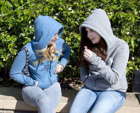 Two teenage girls laughing and talking