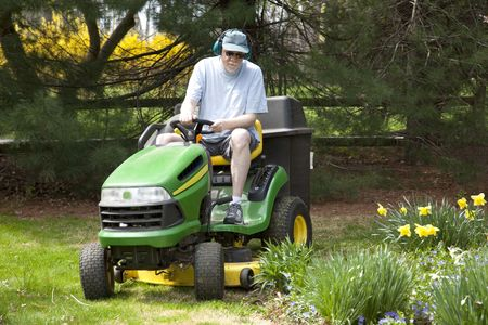 Middle-aged man riding lawn mower photo