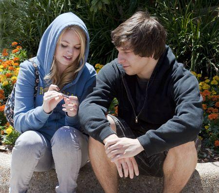 Adolescentes joven sentados juntos fuera, hablar