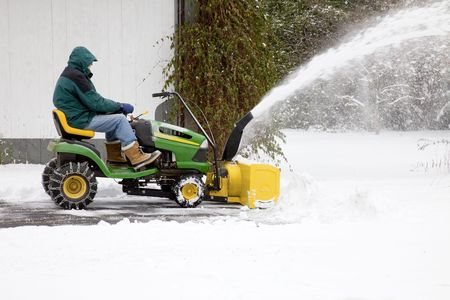 snow clearing: Side view of middle-aged man on riding snow blower, clearing snow out of residential driveway