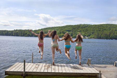 Vier tienermeisjes springen van een dok in Little Squam Lake - terug Stockfoto
