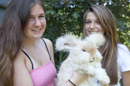 lapin: Deux adolescentes souriant tenant flop à oreilles de lapin angora Banque d'images