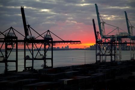 Lading kranen en zons ondergang op poort van Miami, Florida