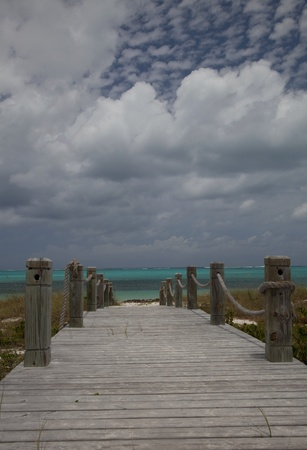 bight: Weathered wooden walkway leading to white sand and blue-green water of Bight Beach, Grace Bay, Providenciales, Turks & Caicos Islands.  Interesting popcorn clouds in blue part of sky. Stock Photo