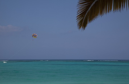 identifiable: Two people parasailing over blue-green water of Grace Bay, Providenciales, Turks, Caicos Islands, on a beautiful, sunny day.  Peoples faces are not identifiable.
