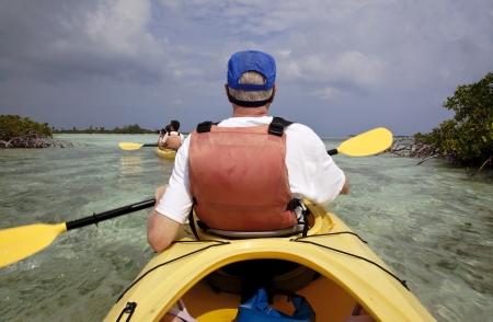 Oudere man van middelbare leeftijd en twee oudere kinderen kajakken door de mangroves uit Providenciales, Turks-en Caicoseilanden