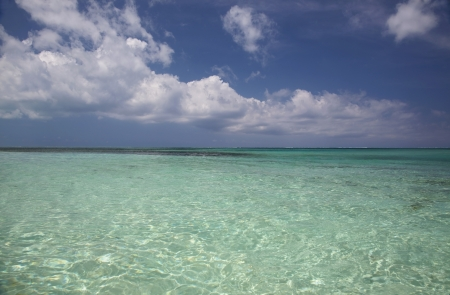 Beautiful clear, blue-green water at Smiths Reef in Grace Bay, Providenciales, Turks and Caicos Islands.  A deep blue sky with puffy white clouds accent a perfect day.