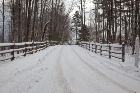 on both sides: Snow-covered fence lining both sides of a snowy driveway in New Hampshire Stock Photo