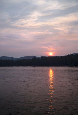 Oranje zon boven Little Squam Lake, NH Stockfoto