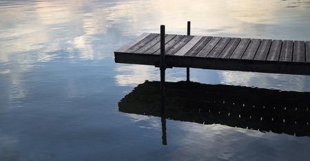 Dock op een meer met wolken weerspiegeld in het water Stockfoto