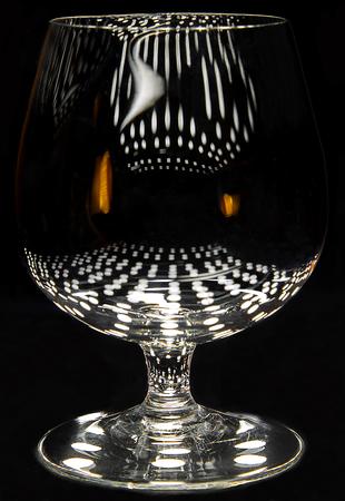 Kleine cognac borrel (drie duim hoog) met lichtreflecties