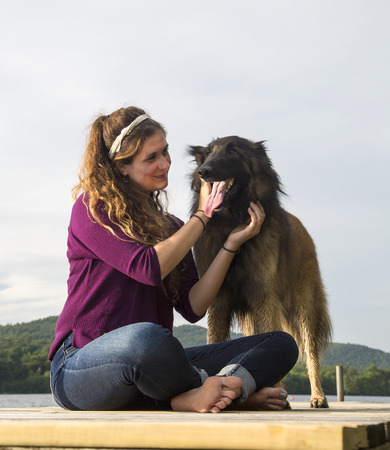 Young woman smiling at her dog on a dock at a lake