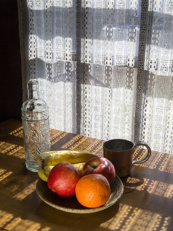Bowl of fruit, empty bottle, and copper cup on a table in dappled light coming through a lace curtain