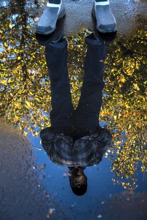 Reflectie in een plas man omlijst door de herfst bladeren op een boom