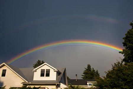 Zeer levendige hoofdregenboog met dowere tweede regenboog boven het over voorstedenhuizen