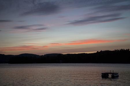 Zonsondergang en kleurrijke wolken over Squam Lake, New Hampshire Stockfoto