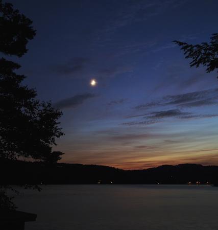 Kleine Crescent Moon over Squam Lake, New Hampshire, na zonsondergang Stockfoto