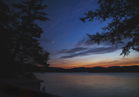Kleuren aan de horizon nadat de zon ondergaat, met een kleine toenemende maan op Stockfoto