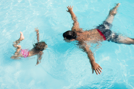 Father and daughter dive into the pool. Synchronous underwater acrobatics.