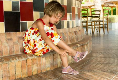 sandalias: Niña que pone en sandalias.
