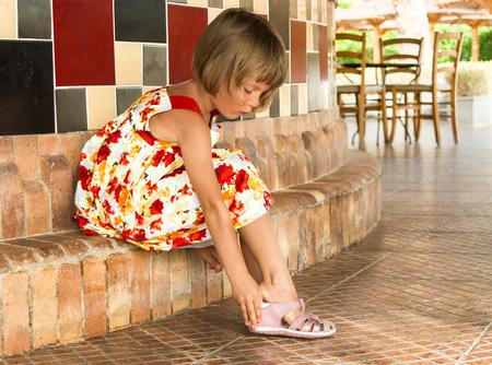 어린 소녀는 분홍색 샌들을 착용.