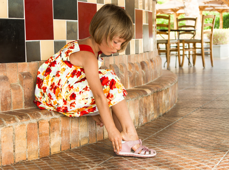 wearing sandals: Little girl wears pink sandals.