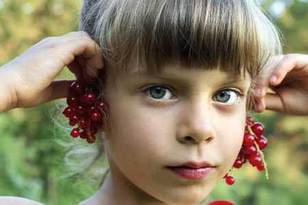 Beauty girl tries on earrings from red currant berries. Stock Photo