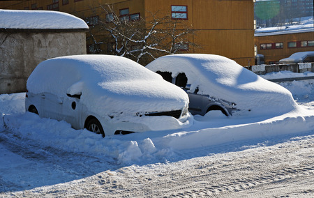 Two parked cars under a large layer of snow.