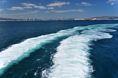 Double white trace on the Mediterranean Sea behind a boat sailing from the port of Ceuta.Maroko, Africa.