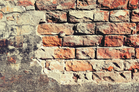 brick wall with peeling plaster and a metal nail in the middle of the image Stock Photo - 124936752