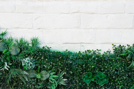 white brick wall with green artificial flowers for texture, background, text or image 写真素材