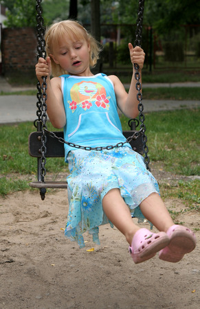 Pretty childhood girl on the swing in the park photo