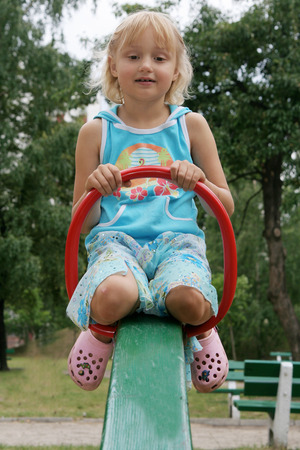 swaying: PrPretty childhood girl swaying on the balance swing