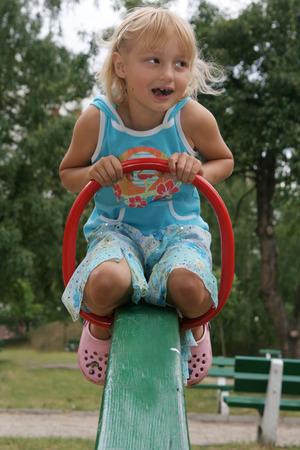 Pretty childhood girl swaying on the balance swing Stock Photo - 1875173